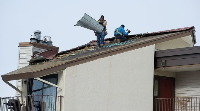 Miguel Uribe removes a piece of roofing while working with Pablo Campoverde at the Spring Meadows condominiums in Steamboat Springs on Friday. The employees of High Point Roofing LLC were called in to replace the roof after Thursdays high winds caused significant damage to the building. High Point owner Jeremiah McGuire said he had 40 calls for repairs after Thursdays windy weather.