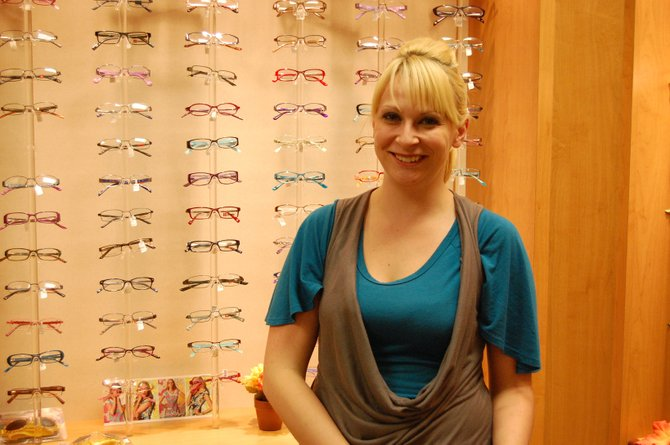 Ellisa Doolin displays the selection of eyeglass frames available at her workplace, Eyecare Specialties, 1111 W. Victory Way, Ste. 110. Doolin, 24, began working as a receptionist at the optometry outlet about six months ago. She said she enjoys her job because of the friendly atmosphere.