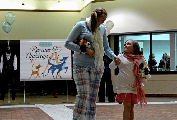 Craig resident Trynity Hummel, 7, looks up at Jordan McLeslie, 17, as they walk the runway during Saturday's third annual Rescues and Runways fundraiser at Centennial Mall, 1111 W. Victory Way. The event, which is sponsored by Maurices women's clothing store, raised more than $1,700 for the Humane Society of Moffat County.
