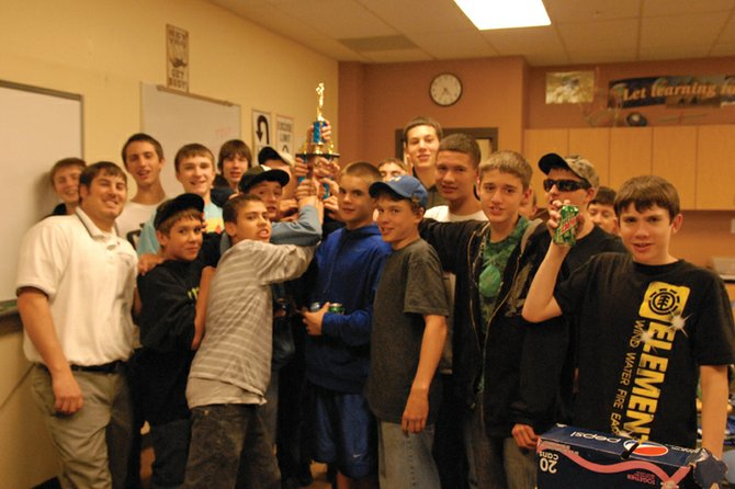 Members of the Craig Middle School eighth-grade boys basketball team hoist the district championship trophy during a victory party Tuesday in coach Drew Morris's classroom. The team took first place in the district tournament, beating Steamboat Springs 39-30 in the final round.