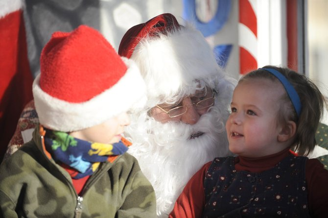 Tim, 5, and sister Jessica Bedell, 3, visit Santa on Saturday in front of the Routt County Courthouse.