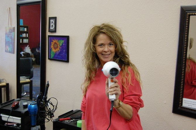 Stylist Julie Camp holds her trusted hair dryer at her work station at Wildflowers Salon, 1596 W. Victory Way.