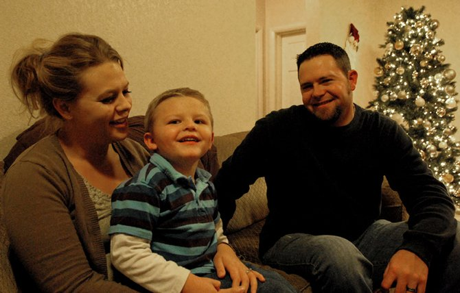 Megan, Kelton and Steve Mudge sit inside their home in Craig. When Kelton was born, Megan and Steve were told their son would live in a vegetative state because of complications he endured while in the womb. But, Kelton proved them wrong: he recently graduated from Horizons Specialized Services' Early Intervention program, where he learned basic motor and communication skills.