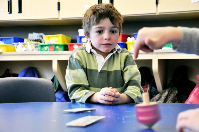 Soda Creek Elementary School kindergartner Henry Magill watches a dreidel spin on his desk Thursday. Henry and his classmates learned about Hanukkah.