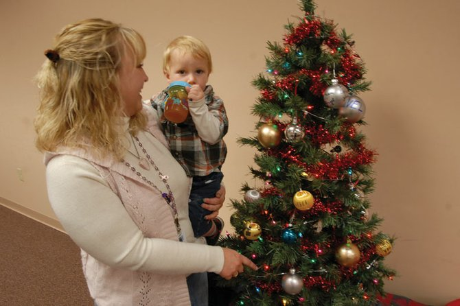 Maria Mosman points out the ornaments placed by her family to her 19-month-old grandson, Austyn Sullivan during the Celebration of Life Tree event Thursday at the Northwest Colorado Visiting Nurse Association. Mosman, a hospice nurse, and her family were among the people who honored loved ones with a personalized ornament.