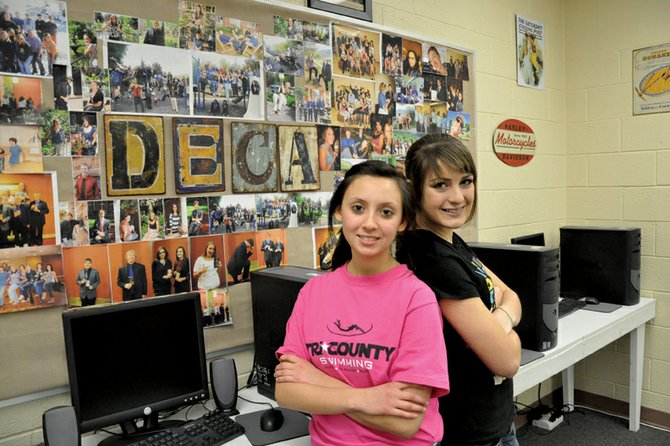 Elisa Teeter, left, a Moffat County High School sophomore, and Moriah Mecham, a freshman, pose in front of a collection of photos of the school's Distributive Education Clubs of America group. Teeter and Mecham are among 21 students who qualified for the DECA state competition, scheduled for Feb. 25 through 28 in Colorado Springs.
