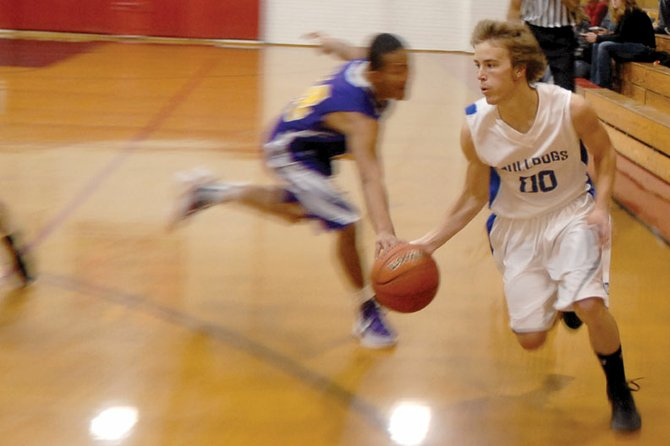 Taft Cleverly, a Moffat County High School sophomore guard, dribbles past a Denver North defender Saturday during the Black Canyon Classic at Montrose High School. The MCHS boys varsity basketball team went winless in the tournament.