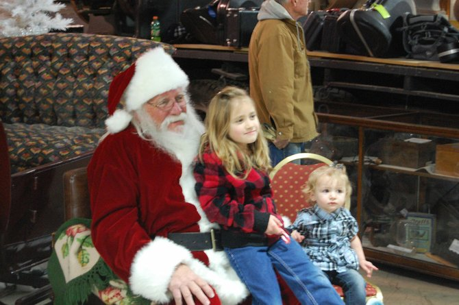 Alea Duran, 7, left, and cousin Breanna Ginther, 1, meet Santa Claus during Saturday afternoon's Christmas for Kids event at Wyman Museum. The festive event included crafts, music and other holiday-themed family activities.