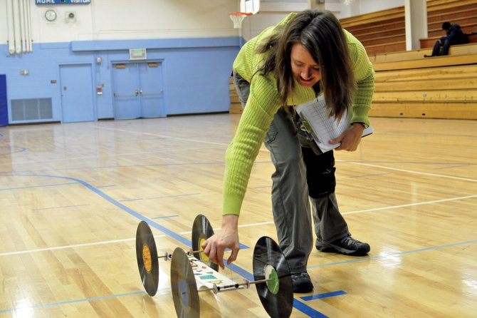 Sandy Sorensen, Craig Middle School seventh- and eighth-grade science teacher, examines eighth-grader Ian Day's mousetrap car Tuesday morning during the school's annual mousetrap car rally in the CMS gym. The event was part of a physics unit that included lessons about simple machines, like levers, wheels and axles.