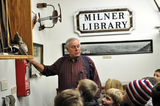 Lou Wyman, owner of Wyman Museum, shows Sandrock Elementary School third-graders a vintage gum machine Wednesday afternoon at the museum. Students visited the museum to wrap up a unit that simulated life in an 1800s one-room schoolhouse.