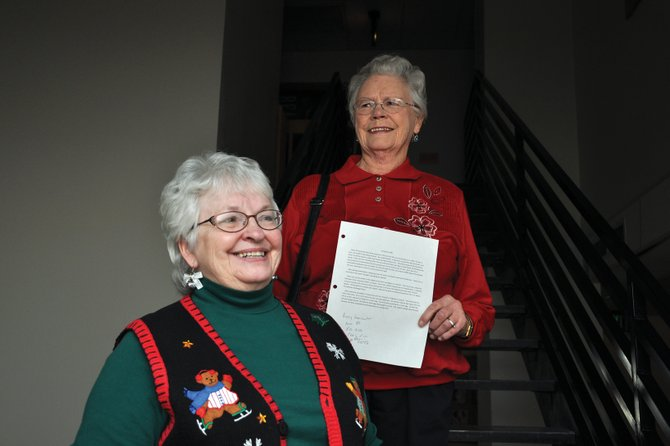 Lois Stoffle, left, of Maybell, and Peggy Gonzales, who lives south of Craig, share a smile Friday morning in the Colorado Northwestern Community College Bell Tower Building while holding memoirs they wrote for a class offered by the college. They are among several area residents who wrote memoirs recounting Christmas memories.