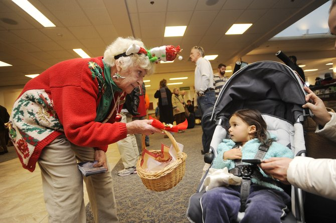 Steamboat Springs Chamber Resort Association visitor information specialist Donna Hellyer offers a candy cane to 2-year-old India Castellino, of Los Angeles, on Friday at Yampa Valley Regional Airport. Officials say passenger numbers at the airport this ski season are up more than 5 percent from last year.