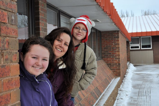 Amanda Reed, center, a Craig-area resident, poses with her children, Caitlin, 11, and Trayton, 9, at Sunset Elementary School, where Trayton goes to school. Reed volunteers at Sunset Elementary and also helps put on an annual holiday store at local elementary schools that allows children to buy affordable gifts for their families.