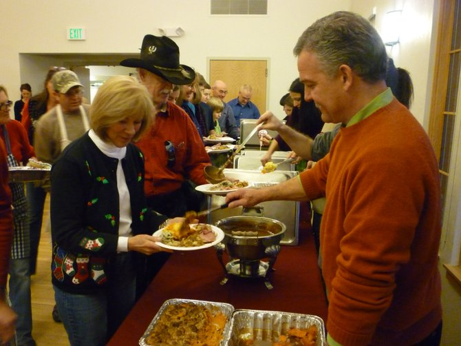 Realtor Tim McCarthy serves Steamboat resident Judy Tudor during the 20th annual Steamboat Springs Board of Realtors Community Christmas Dinner. Tudor attended the dinner with her boyfriend, Hawkin Ludlum, standing to her left, and his family.