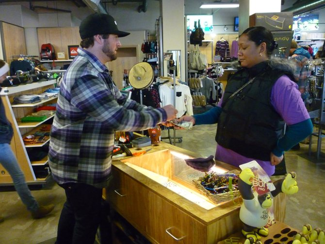 Quicksilver General Manager Derek Cullen hands change Monday afternoon to Hoku Parker, of Steamboat Springs, after she bought a beanie at the store. Quicksilver was one of several businesses that opened Christmas Day and reported strong holiday sales.