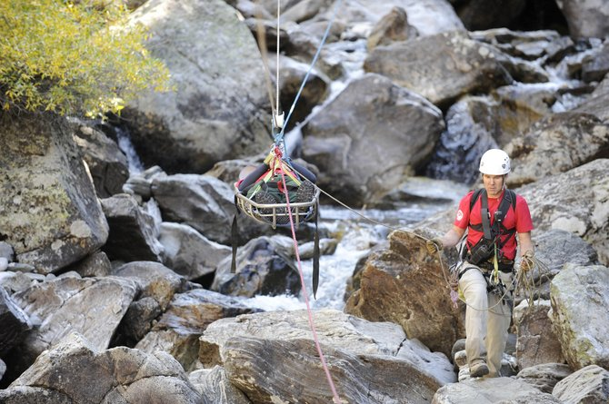 Routt County Search and Rescue President Russ Sanford guides a basket carrying Search and Rescue volunteer Marc Bell during a training exercise last year. Sanford and other Search and Rescue leaders are looking for volunteers for the organization.