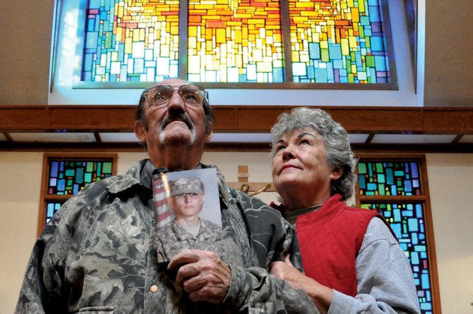 "Ken ""Howdy"" Davis holds a picture of his grandson, Dylan Correia, with Fran Davis, his wife of 23 years, at his side Friday morning at St. Michael Catholic Church. Correia, a private first class with the U.S. Army, surprised the local couple with an unexpected visit Christmas Eve during a leave from his deployment in Afghanistan."