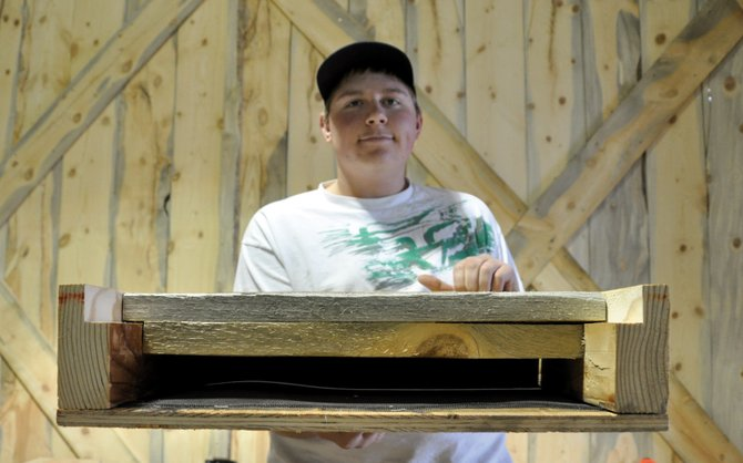 Seth Morgan, 16, a member of the Elkhead Wranglers 4-H club, holds up a bat box he and other club members made Thursday. The boxes have a narrow opening to keep predators out and are lined with screen so the bats can crawl inside.