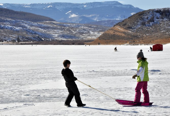 Dominic DeSiato pulls his sister Bella on a sled Sunday on top of a frozen Stagecoach Reservoir. Stagecoach State Park hosted several hikers and ice fisherman on a New Year's Day marked by clear skies and warmer temperatures.