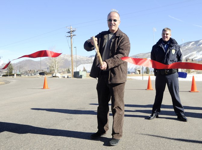 Joel Rae watches retiring Steamboat Springs Police Department Chief JD Hays cut a ribbon during the JD Hays Way street dedication ceremony Thursday. Rae has been named the new police chief.