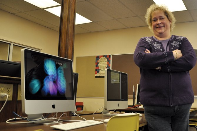 "Christine Balderston, Moffat County School Board secretary, poses in a computer lab Thursday at Moffat County High School. She believes preparing students for a digital world is a challenge the school board faces as it dives into the new year. ""They're going to have to be able to live in a world that uses technology all the time,"" she said."