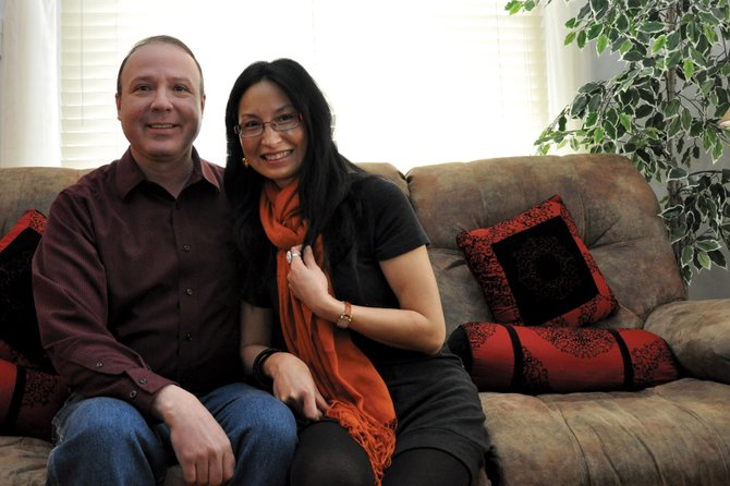 Owen Jenrich and his wife, Mei, pose for a photo together Friday morning in their Craig home. Mei was a successful accountant in the Chinese city of Baoding when she met Owen online in 2007. They courted via the Internet and met several times in China before marrying in December 2008.