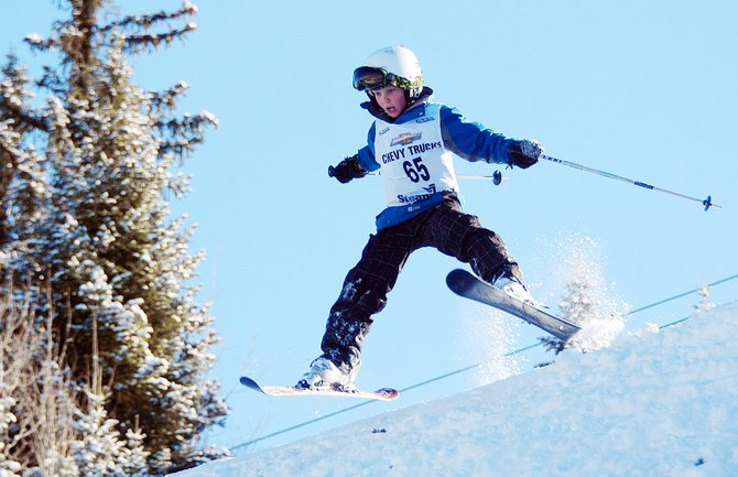 Xander Tatar-Brown kicks into a spread eagle after flying off the jump during a freestyle moguls competition Sunday at Howelsen Hill in downtown Steamboat Springs. The event attracted 100 young athletes from across the region for two runs down the moguls course on the hill.