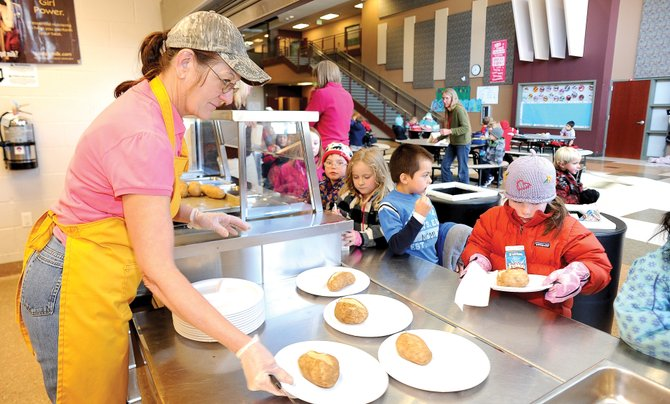 Rebecca Witham serves kindergartners at Soda Creek Elementary School during lunch Monday. The Steamboat Springs School Board will take two more weeks to mull the district's bid to become Colorado Mountain College's Alpine Campus' food service provider after board members couldn't reach a consensus on the proposal Monday night.
