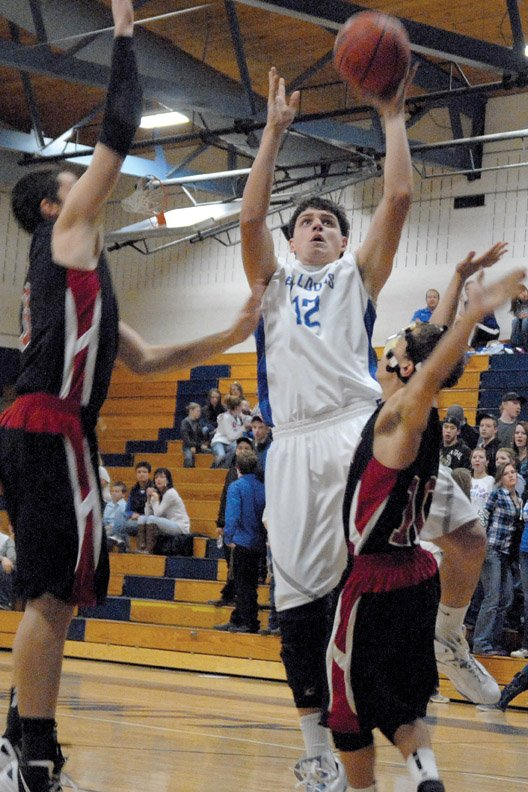 Andy Browning, a Moffat County High School senior, elevates over an Aspen High School defender Tuesday at MCHS. The MCHS boys varsity basketball team got out to a fast start, but couldn't make the correct adjustments in the second half in a 66-46 loss.