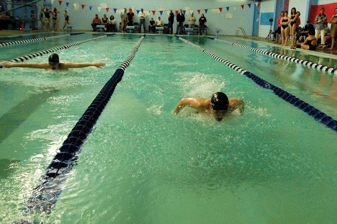 Eryn Leonard, right, a Moffat County High School senior, leads the way during the 100-meter butterfly event Saturday against Delta at MCHS. Leonard swam her way to one of 10 first-place finishes for the MCHS girls varsity swimming team en route to a 633-527 victory.