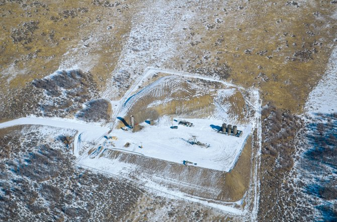 Quicksilver's Pirtlaw oil well on Wolf Mountain is seen Jan. 13 from the air. Of the three dark cylindrical storage tanks in the right of the frame, one is used for storing well fluids and the other two are devoted to storing oil, according to a company official. The pump jack at the well is not currently operating, according to the same source.