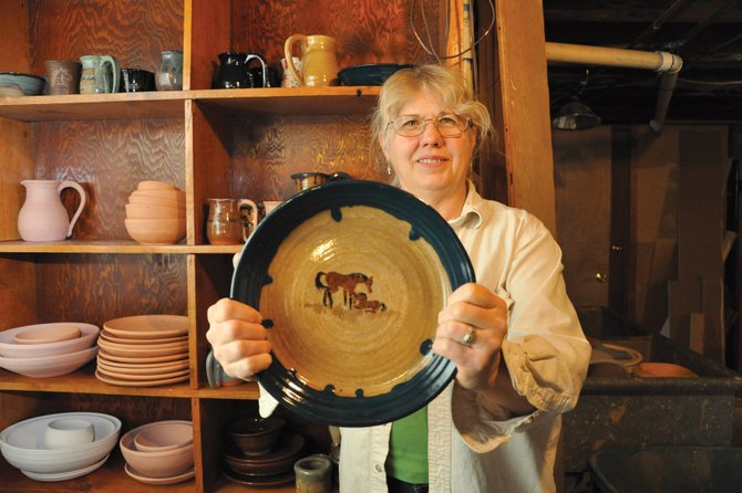 Deb Coniff displays a dish she made as she stands in the basement of her Craig home. Coniff has been teaching art off and on since she was in her teens and with more free time on her hands now, she hopes to eventually make it a full-time occupation.