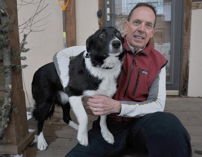 Mel Stewart, acting deputy fire chief of Steamboat Springs Fire Rescue, sits on the step of his neighbor's home with Spike, an 8-year-old border collie, he rescued from the frigid waters of the Yampa River on Wednesday evening.