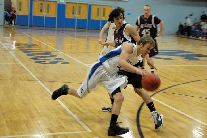 Taft Cleverly, a Moffat County High School sophomore, dribbles around a Palisade defender Saturday at MCHS. Cleverly said the MCHS boys varsity basketball team struggled against Palisade's man-to-man defense in a 51-31 loss.