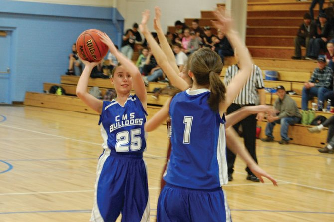 Eighth-grader Erin Fagan, right, attempts to set a pick for teammate Shelby Fliniau as she passes the ball during the Craig Middle School girls basketball team's Thursday home game against Soroco. The team continued its undefeated season with a 51-14 win.