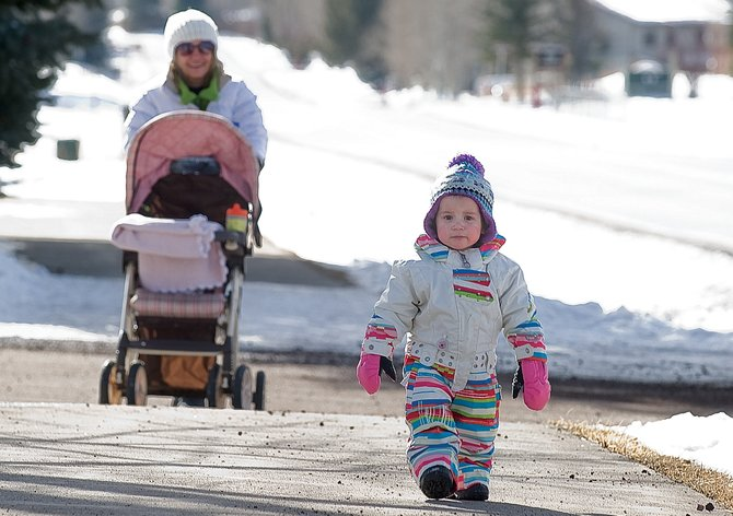 Kamilla Victoria, 15 months, takes advantage of Monday's mild weather to take a walk along Whistler Road with her grandma Maria Numes.