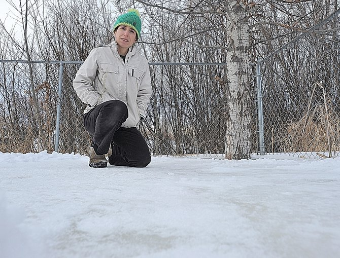 Cindy Ruzicka kneels on several inches of ice that have formed on the ground of her home, which backs up to the wetlands between Honeysuckle Lane and U.S. Highway 40 in west Steamboat Springs.