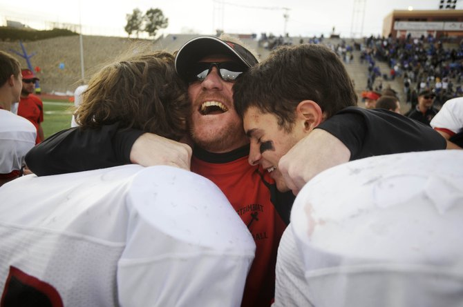 Jerry Stabile celebrates in 2009 with Steamboat Springs High School football players Bryce Mayo, left, and Mitchell Lekarczyk after a win. Stabile, who was promoted to police captain Thursday, has served as a role model for hundreds of local youths.