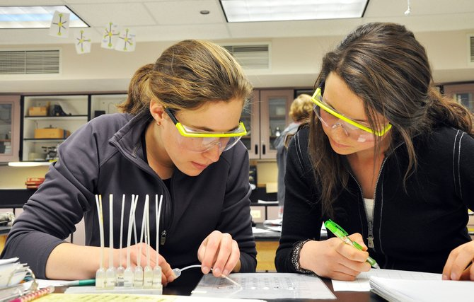 Steamboat Springs High School skiers Martha Anderson, left, and Lucy Newman mix chemicals Monday during a chemistry class. New technology and efforts by teachers are making it easier for winter athletes to excel academically even though they miss several days of school.