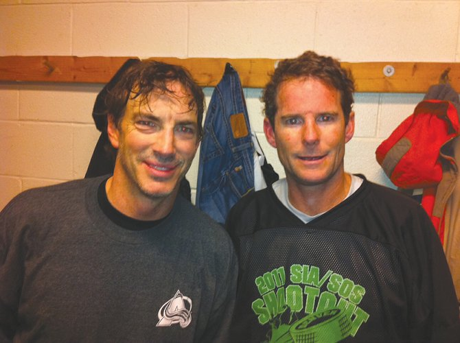 Eugene Buchanan and former Colorado Avalanche star Joe Sakic hang out after a hockey exhibition during the 2011 SIA trade show in Denver.
