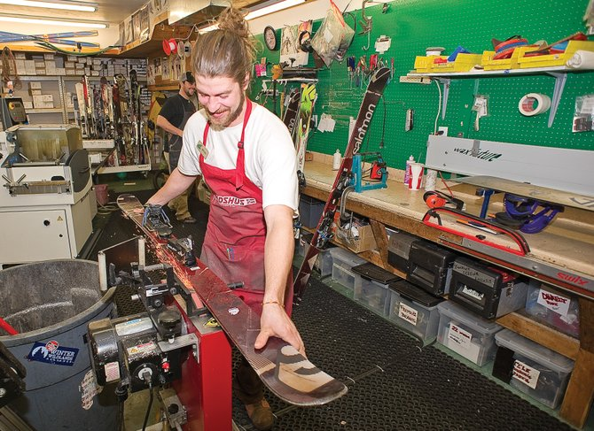 Kellen Johnson, a ski and snowboard technician with Ski Haus, tunes skis Friday afternoon. Several local ski shops are seeing a boost in different segments of their business, such as ski tuning, because of the lack of snow this season.