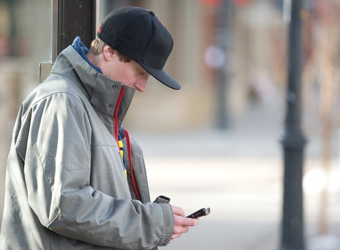 Jeff Sundwall uses his smartphone while waiting for a bus Monday in downtown Steamboat Springs. Some Routt County residents have been improperly charged city sales taxes for their wireless service. Those residents are eligible for a refund.