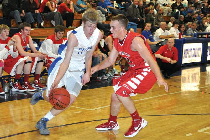 Colby Haddan, a Moffat County High School senior, dribbles around a Glenwood Springs defender Tuesday at MCHS. Haddan scored 15 points to help lead the MCHS boys varsity basketball team to a 78-56 rout of the Demons.