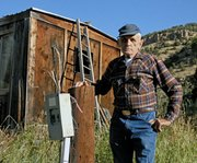 Ray Wagner, 87, stands beside a disconnected electrical box and chopped utility pole in Sept. 2011 at his ranch in Hamilton. Wagner contends Yampa Valley Electric Association unlawfully removed the electrical service from his home, shop and well-house. His son, Jay, filed a lawsuit against YVEA last month in Moffat County District Court. 