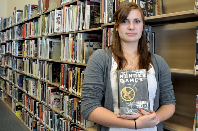 "Darby Andrews, a Moffat County High School junior, holds a copy of Suzanne Collins' ""The Hunger Games"" in the high school library. When Andrews, 17, learned the school selected the book for its inaugural ""One Book, One MCHS"" reading program, she was the first to sign up. ""I got a bunch of my friends to sign up so we can talk about (the book) after we've read it,"" she said."