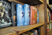 "Copies of ""Catching Fire"" and ""Mockingjay,"" the second and third installments, respectively, of Suzanne Collins' popular trilogy, sit on a shelf Thursday at Downtown Books. Novels in the futuristic series were a hot item at the bookstore this Christmas, and they are among the shop's most popular books, employees said."