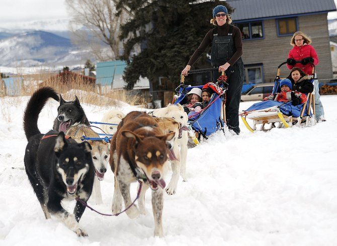 A team of dogs mostly composed of Iditarod finishers rounds a corner on a snowy field next to South Routt Elementary School on Wednesday. Tami Thurston offered rides to students, helping cap off lessons theyd been learning about the dogs and the race.