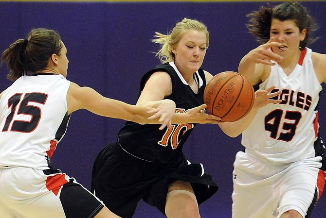 Hayden&#39;s Amber Sather tries to drive the ball between a pair of Paonia defenders Friday. The Eagles dialed up their defense in the second half to surge past the upset-minded Tigers during the district basketball tournament in Kremmling.