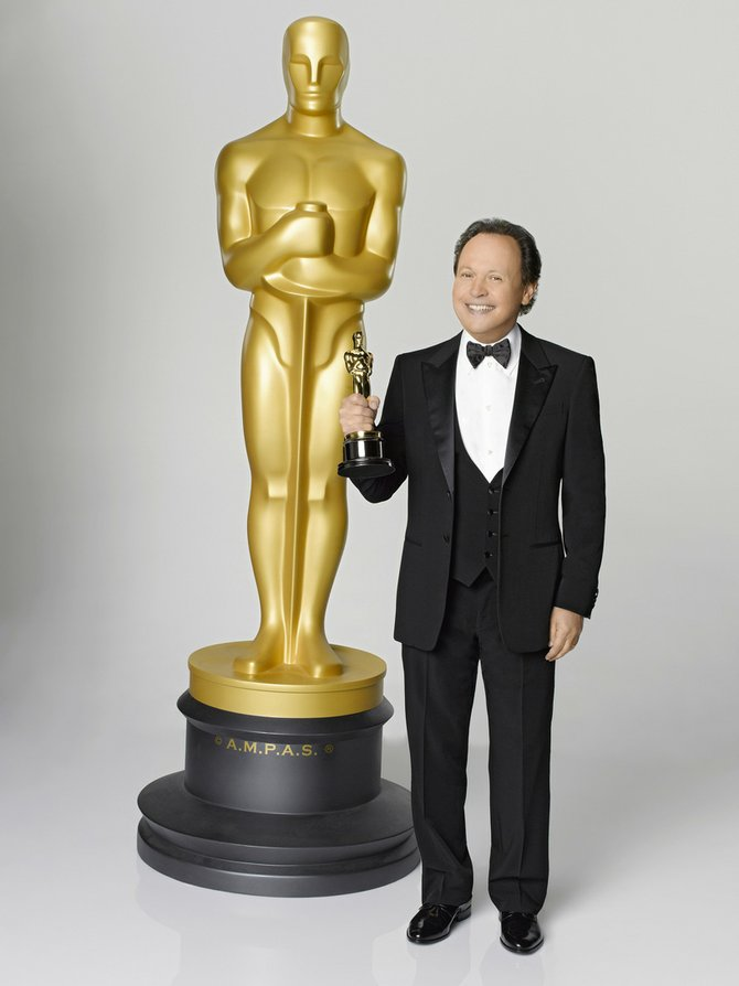 Comedian Billy Crystal hoists an Oscar statuette in front of a much larger model of the movie prize. Crystal will host the 84th Academy Awards, which broadcasts Sunday night on ABC.