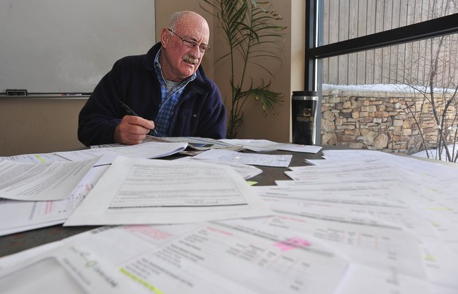 Greg Kammerer looks over the large amount of paperwork he has accumulated as part of his effort to seek a refund for taxes he paid to Verizon Wireless the past five years. Kammerer and other residents living outside the city limits incorrectly were billed for those taxes.